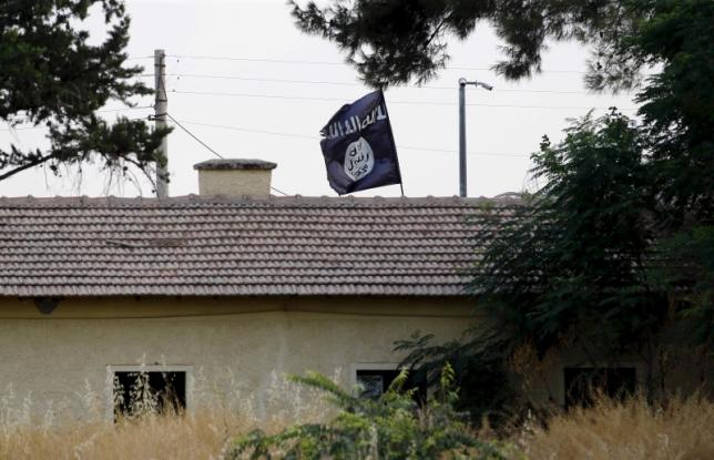 An Islamic State flag flies over the customs office of Syria's Jarablus border gate as it is pictured from the Turkish town of Karkamis